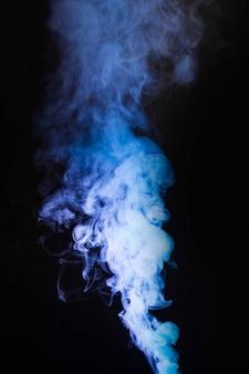 黒い背景の中央にある紫色の煙の煙