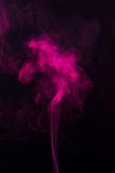 ピンクの煙が黒い背景の上に上向きに移動