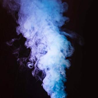 黒の背景の前で太い回転煙