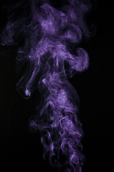 黒の背景に分離された紫色の煙スチーム