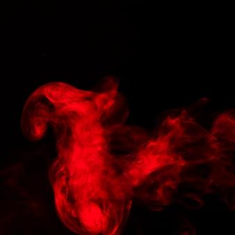 Ярко-красные пары дыма на черном фоне