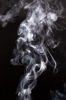 かすかな煙の雲が黒の背景に広がる