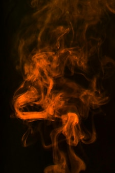 オレンジ色のかすかな煙が黒い背景に広がる