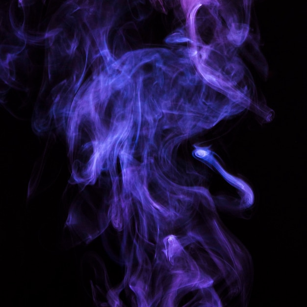 黒い背景に繊細な紫色のタバコの煙の動き