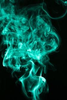緑の煙と霧の黒の背景にふわふわのパフ