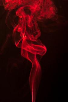 抽象的な赤いカール煙が黒の背景に立ち上がる