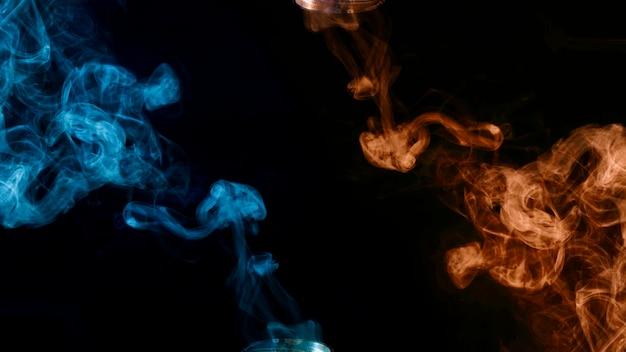 黒の背景に青とオレンジ色の煙の破片