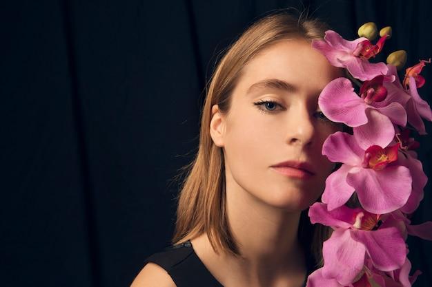 ピンクの花を持つ思いやりのある女性