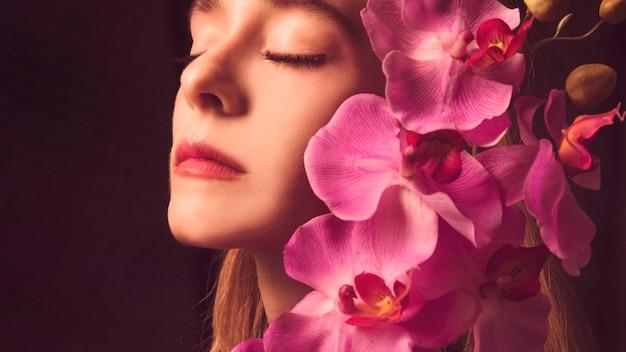 ピンクの花を持つ思いやりのある若い女性