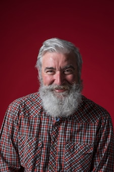 赤い背景に対してカメラを探している灰色のひげを持つシニア男の肖像