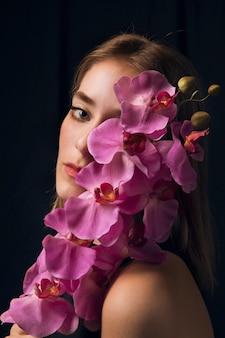 明るいピンクの花を持つ思いやりのある女性