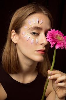 顔とガーベラの花びらを持つ思いやりのある女性