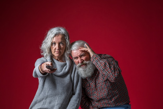 赤い背景に対して一緒にテレビを見ている年配のカップル