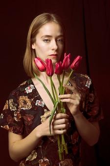 赤いチューリップと思いやりのある若い女性