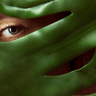 緑の葉で顔を覆っている女
