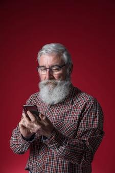 赤い背景に対して携帯電話の地位を使用して灰色のひげを持つシニア男のクローズアップ