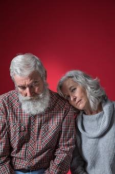 色付きの背景に対して意気消沈した年配のカップル