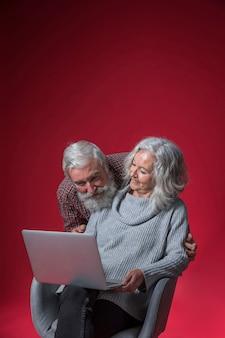 赤い背景に対してノートパソコンを見ている年配のカップルの肖像画