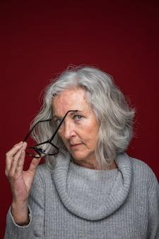 赤い背景に対して手で眼鏡を保持している年配の女性のクローズアップ
