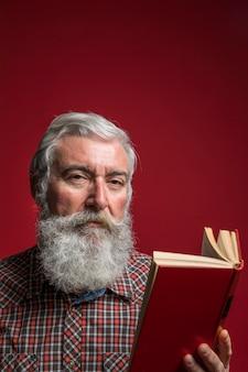Портрет старшего человека с седой бородой, глядя в камеру, держа книгу в руке на красном фоне