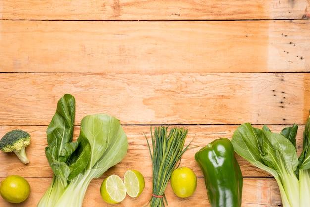 チンゲン菜;ブロッコリ;レモン;ピーマン;木製の机の上のチャイブ