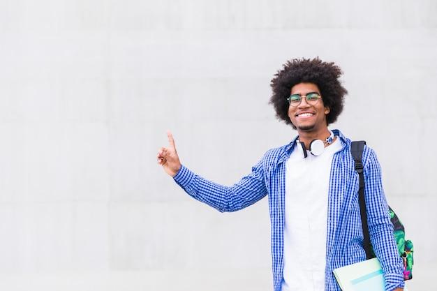 灰色の壁に対して彼の指を指している手で本を持って笑顔のアフリカ人の肖像画