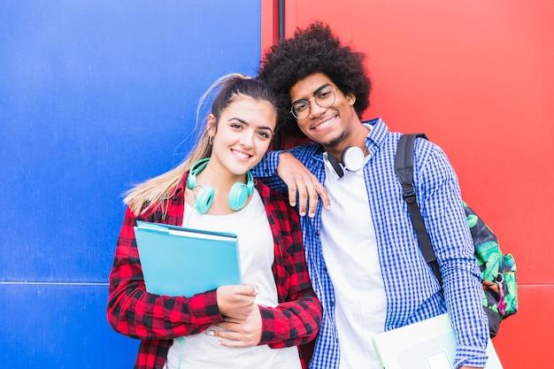 明るい壁に対してカメラを探している若いカップルの笑顔の肖像画