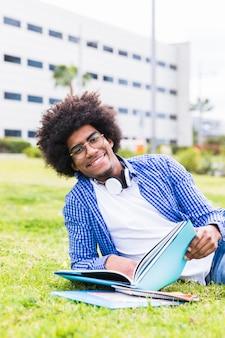 キャンパス地面に横になっている手で本を持って笑顔の大学男子学生の肖像画