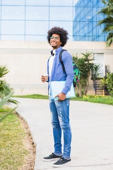 本とキャンパスに立っている使い捨てのコーヒーカップを保持しているアフロ男子学生
