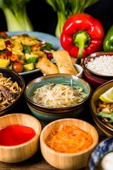 Ростки фасоли в окружении салата; соус; блинчики с начинкой и лапша
