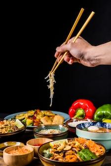 Крупный план руки, используя палочки для еды, чтобы выбрать росток фасоли на черном фоне