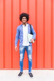 赤い壁に対して手で立って本を持って笑顔の若い男の肖像