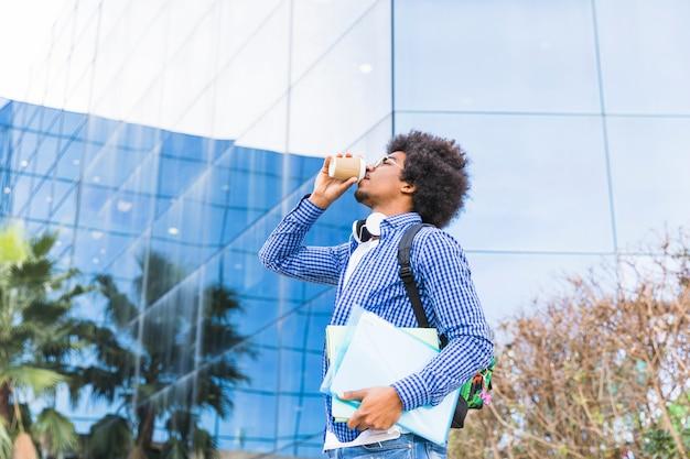 本を手に持って男子学生の建物の前に立っているコーヒーを飲むの低角度のビュー