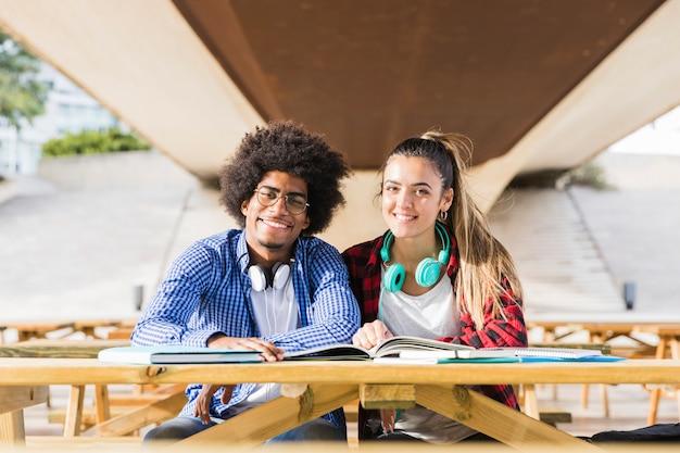 屋外で一緒に勉強して異人種間の若いカップルの肖像画