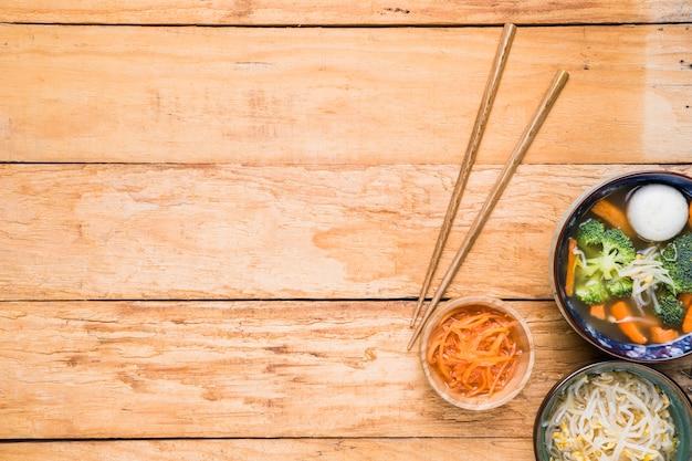 Палочки для еды с тертой морковью; ростки фасоли и рыбный суп на деревянном столе