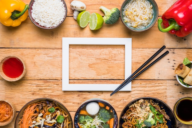 Белая рамка с палочками для еды и тайские традиционные блюда на деревянный стол