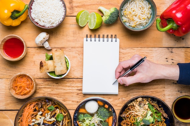 Человек, пишущий на блокноте с ручкой и традиционной тайской едой на деревянном столе