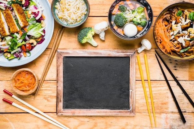木製の机の上のタイのおいしい食べ物とスレートの近くの箸の種類