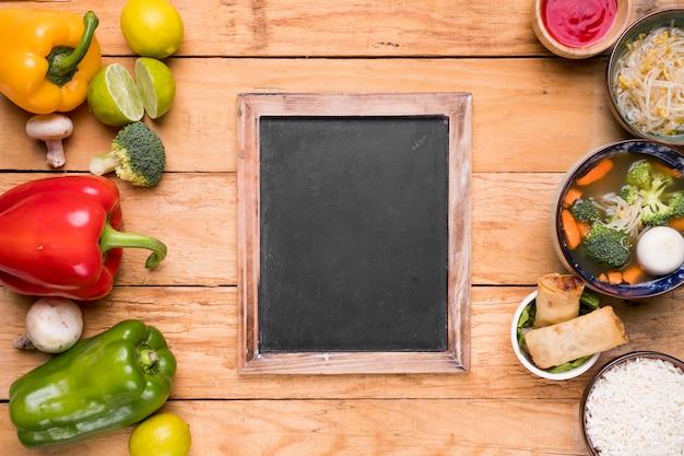 新鮮な収穫野菜と木製のテーブルの上の空白のスレートとタイの伝統料理