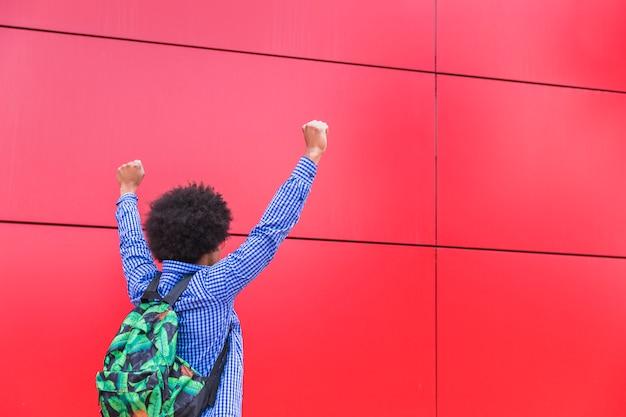 赤い背景の応援に対して後ろに立っている男子学生キャリングバッグの背面図