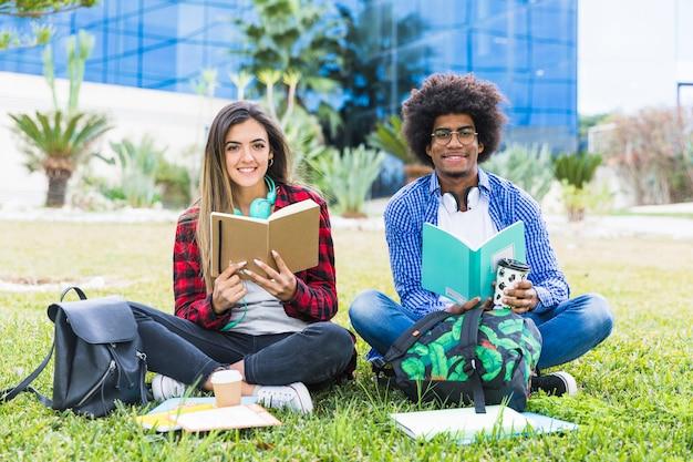 大学のキャンパスで芝生の上に座って本を手で保持している多様な若いカップル