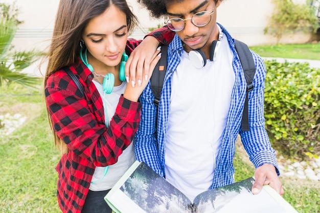 公園で本を読む若い男性と女性の学生のクローズアップ