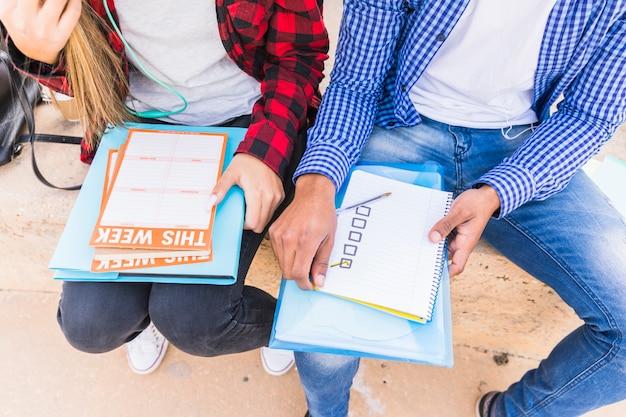毎週のスケジュールを計画している男性と女性の学生の高角度のビュー