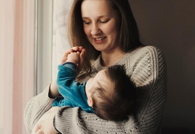 腕の中でかわいい赤ちゃんを持つ幸せな女