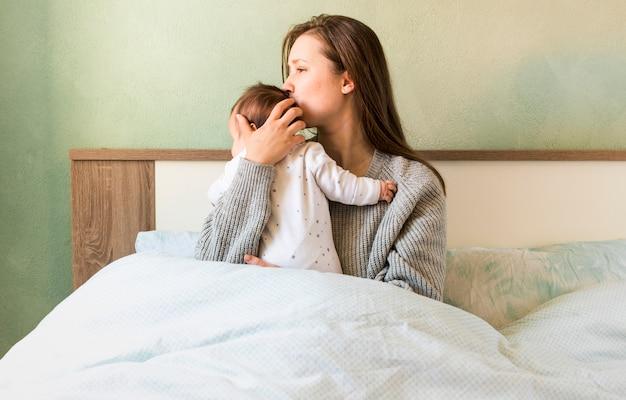 母はベッドの中で腕の中で赤ちゃんにキス