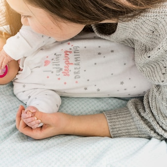 母親と赤ちゃんがベッドの上で手を繋いでいます。