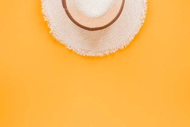 黄色のテーブルの上の麦わら帽子