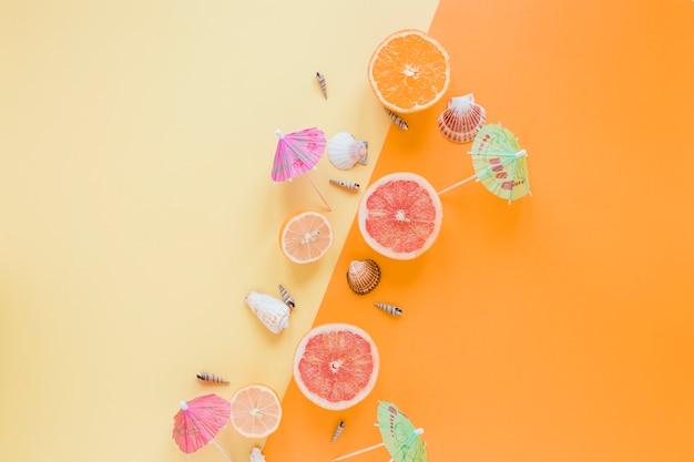 貝殻とカクテルの傘を持つ柑橘系の果物