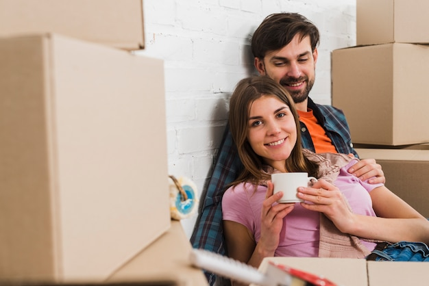 彼らの新しい家で動く段ボール箱の間に座って幸せな若いカップルの肖像画