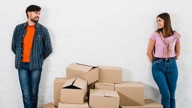カメラを探している壁に立っているスタイリッシュな若いカップルの間の段ボール箱の山